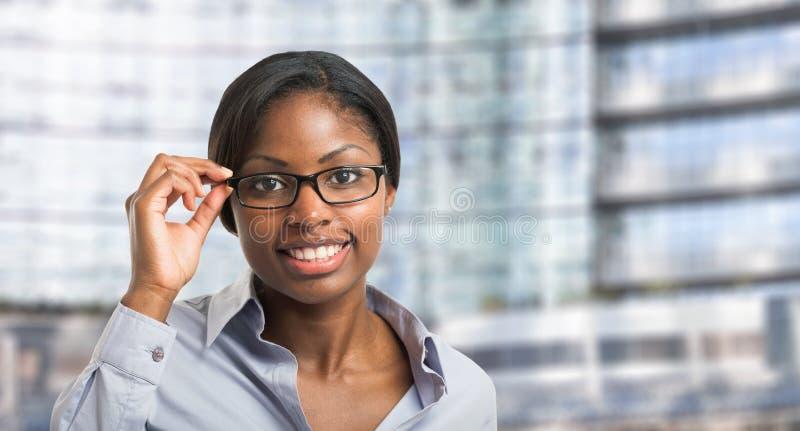 拿着她的镜片的黑人妇女 库存图片