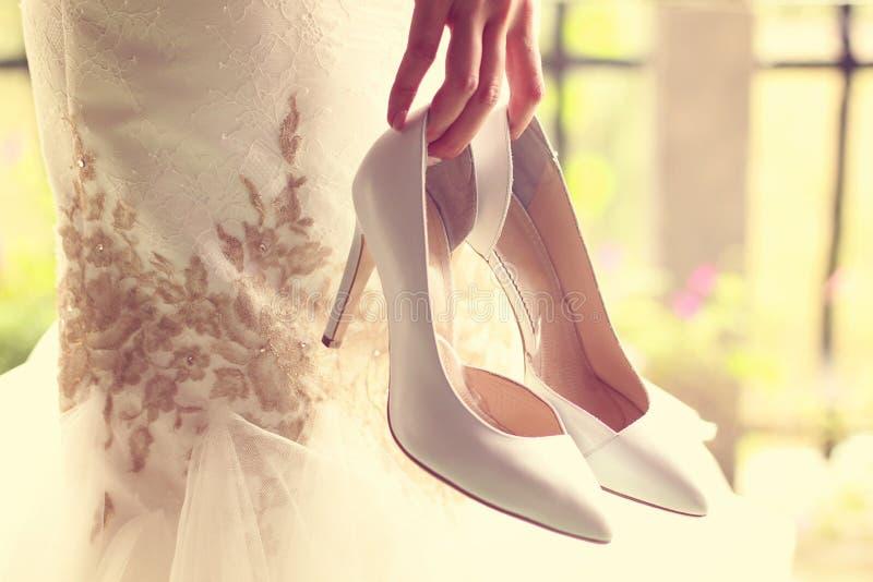 拿着她的鞋子的新娘 免版税库存图片