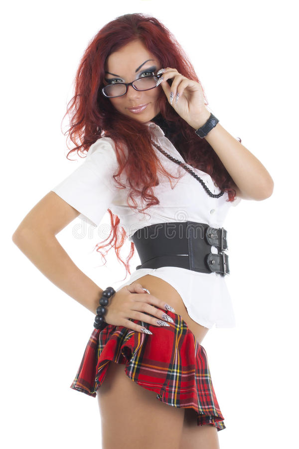 拿着她的玻璃的一条红色裙子的性感的妇女女小学生 免版税库存照片