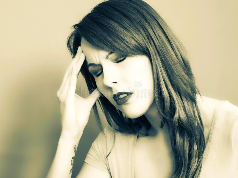 拿着她的头的一个哀伤的沮丧的少妇的被定调子的Portrai  库存图片