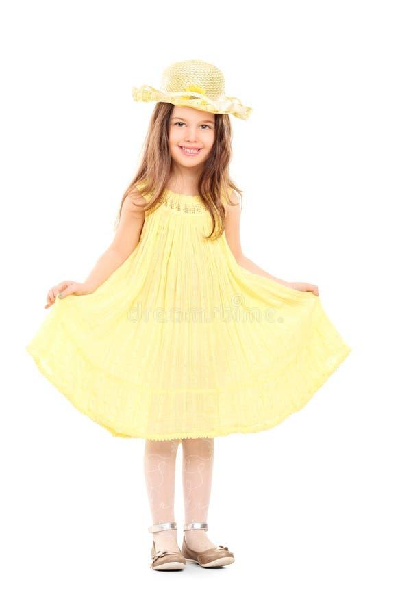 拿着她的黄色礼服的小女孩全长画象 库存照片