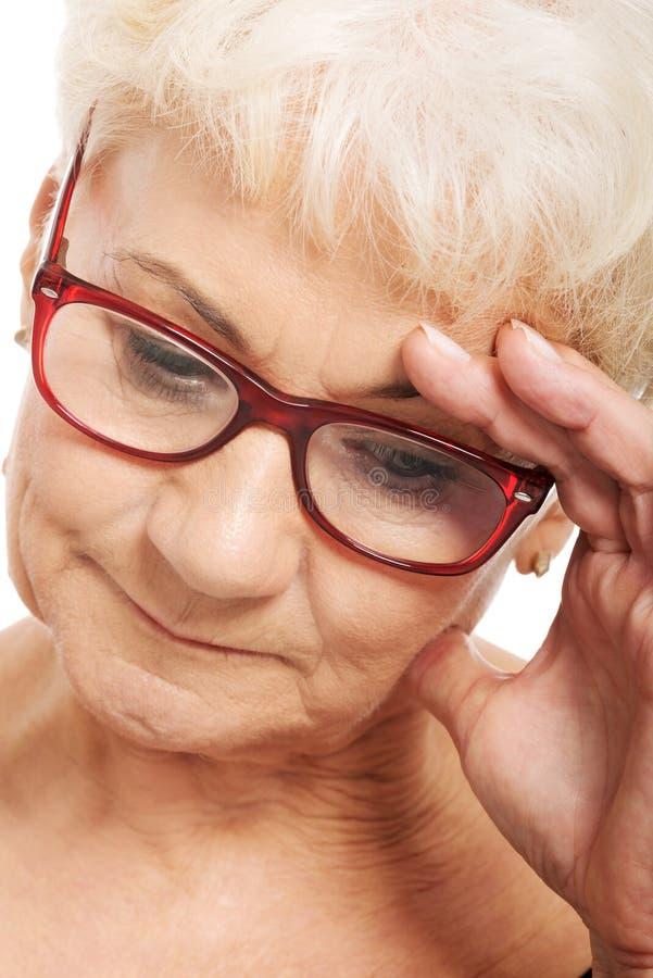 拿着她的头,想法的担心的一个老妇人。 图库摄影