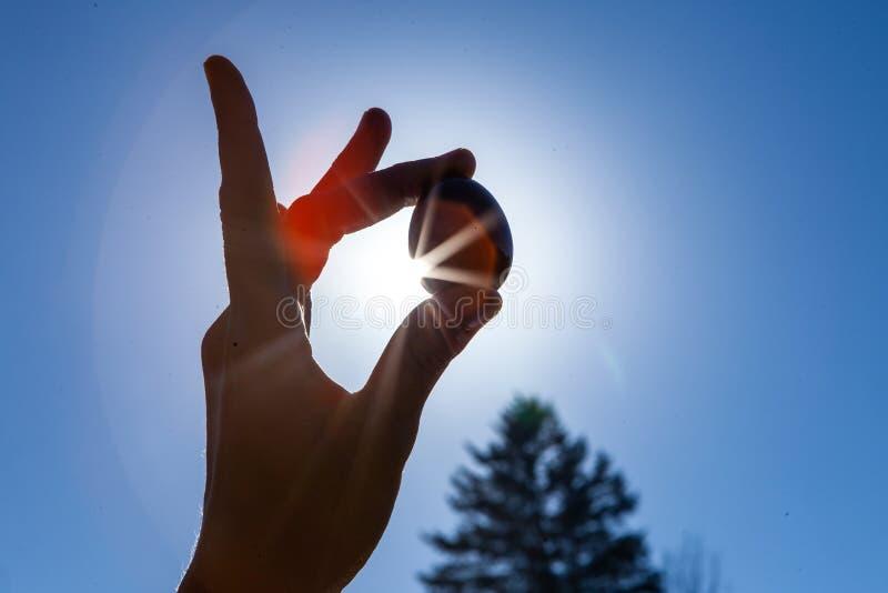 拿着她神圣的yoni玉鸡蛋在天空的年轻女人 免版税库存图片
