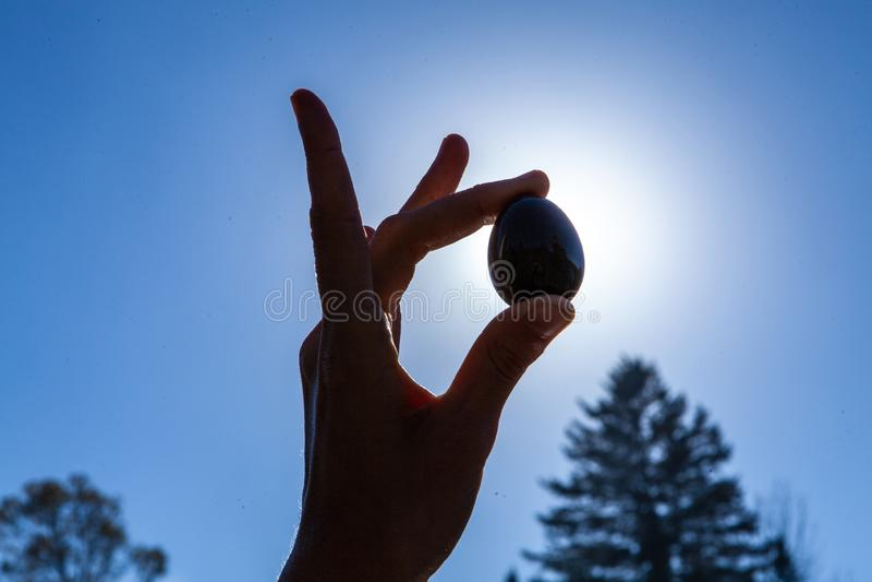 拿着她神圣的yoni玉鸡蛋在天空的年轻女人 免版税库存照片