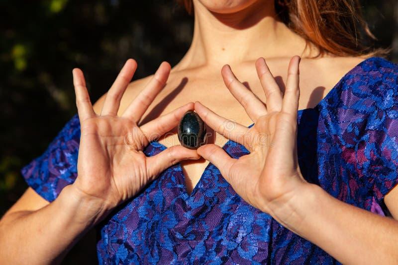 拿着她神圣的yoni玉鸡蛋的年轻女人对她的心脏作为援权标志 库存照片