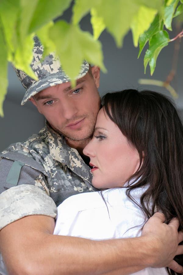 拿着妻子的战士丈夫,在他离开在家前 免版税图库摄影