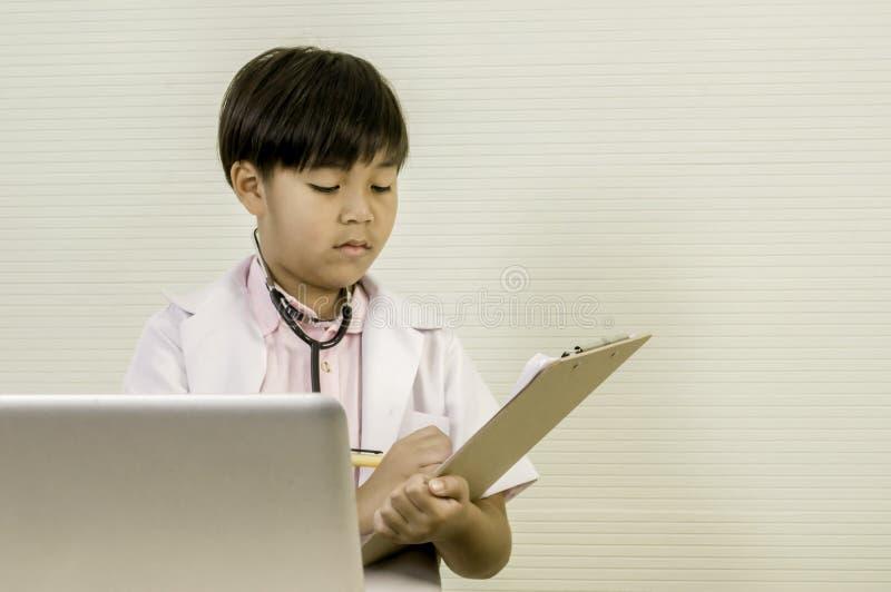 拿着委员会的亚裔小男孩医生,分析耐心数据,在桌安置的膝上型计算机 复制空间 库存照片