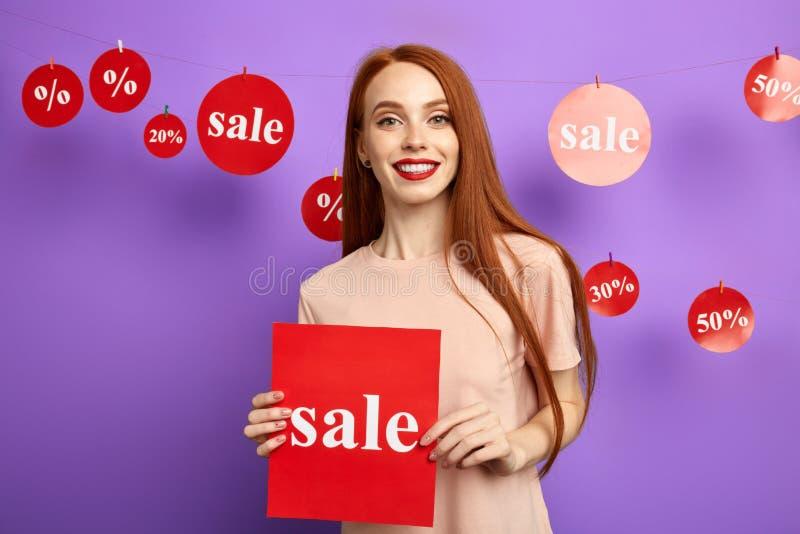 拿着委员会的可爱的年轻女人,显示销售 免版税图库摄影