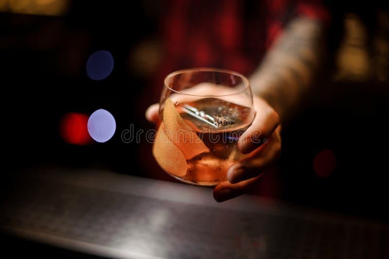 拿着威士忌酒dof杯新鲜的上尉詹姆斯的侍酒者手 免版税库存图片
