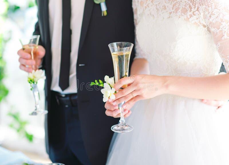 拿着婚姻的香槟玻璃的新娘和新郎 库存图片