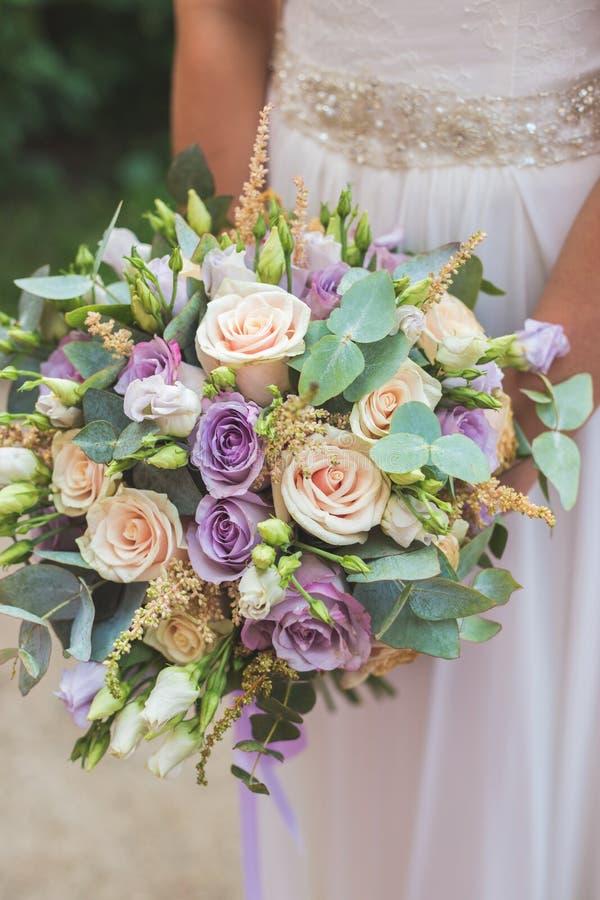 拿着婚礼花束的愉快的新娘照片 库存照片