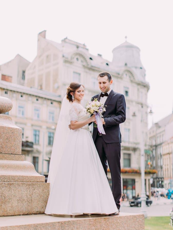 拿着婚礼花束的愉快的新婚佳偶 全长室外照片 免版税库存照片