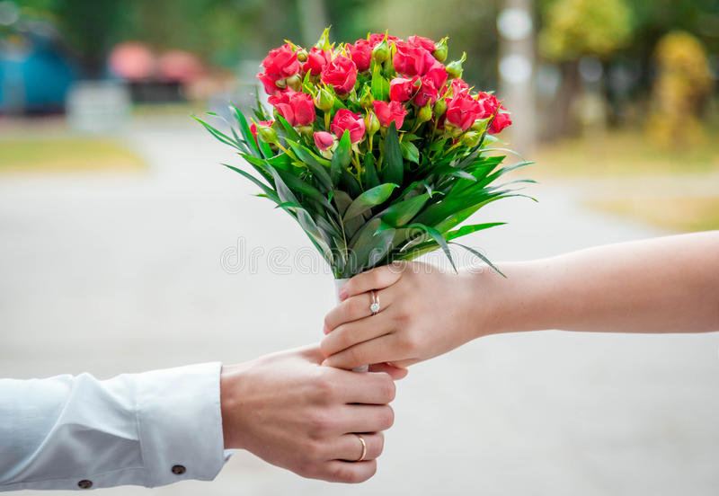 拿着婚礼花束的新娘和新郎的手 免版税库存照片