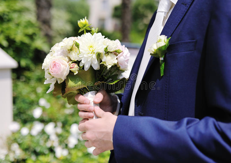 拿着婚礼花束的新郎手 免版税库存图片