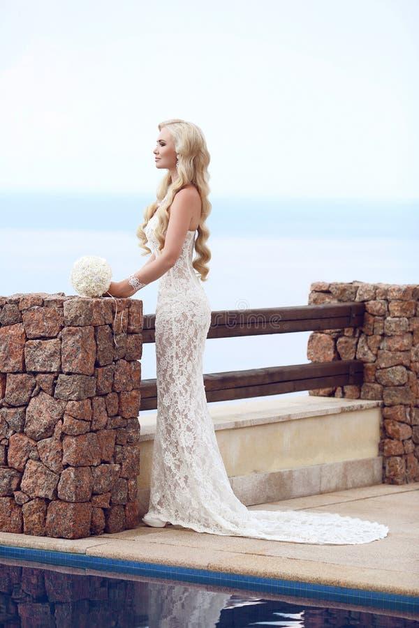 拿着婚礼花束的美丽的新娘画象摆在forma 免版税库存图片