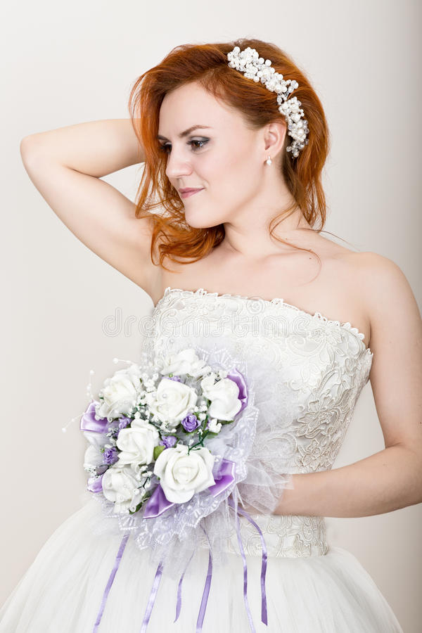 拿着婚礼花束,明亮的异常的出现的婚礼礼服的红发新娘 美好的婚礼发型和 库存照片