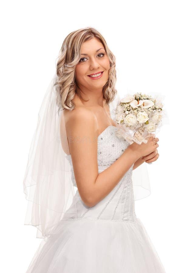 拿着婚礼花的美丽的新娘 免版税图库摄影
