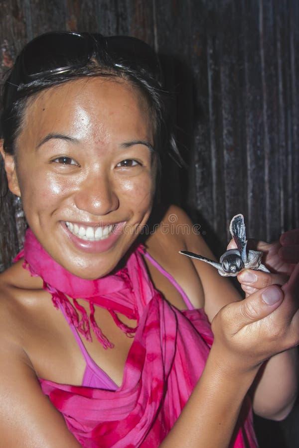 拿着婴孩海龟的女孩 免版税库存图片