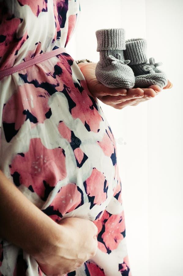 拿着婴孩` s鞋子的礼服的孕妇 免版税库存照片