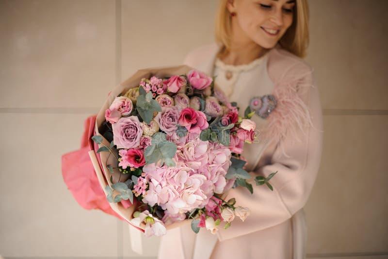 拿着嫩桃红色和白花的花束与绿叶的外套的妇女 库存照片