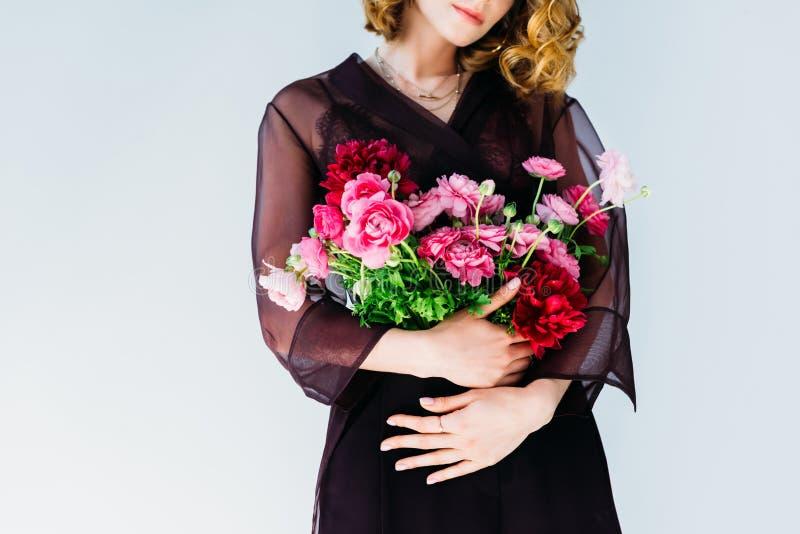 拿着嫩桃红色花的典雅的时髦的妇女播种的射击  库存照片