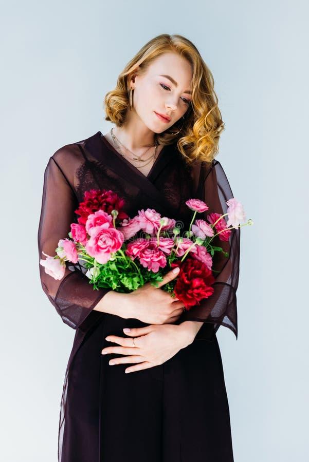 拿着嫩桃红色花的美丽的沉思年轻女人 库存照片