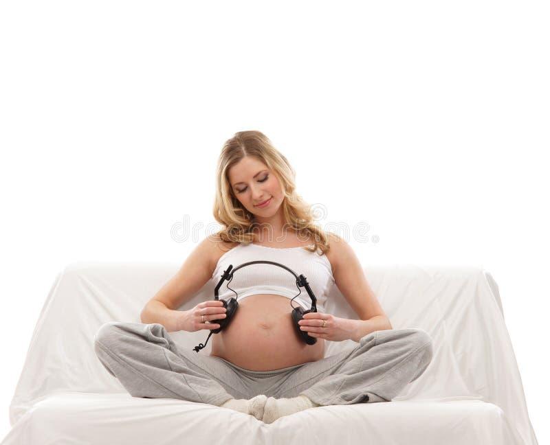 拿着孕妇的白肤金发的耳机新 库存照片