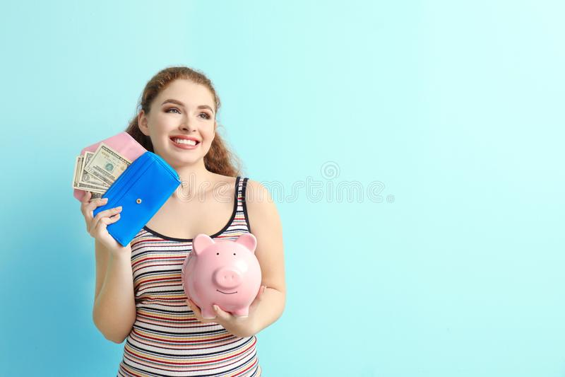 拿着存钱罐和钱包有美元钞票的年轻女人在颜色背景 r 库存照片