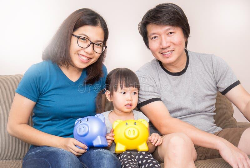 拿着存钱罐的亚洲家庭在客厅 库存照片