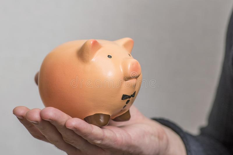 拿着存钱罐的人 拿着存钱罐的人的手 概念存金钱 库存照片