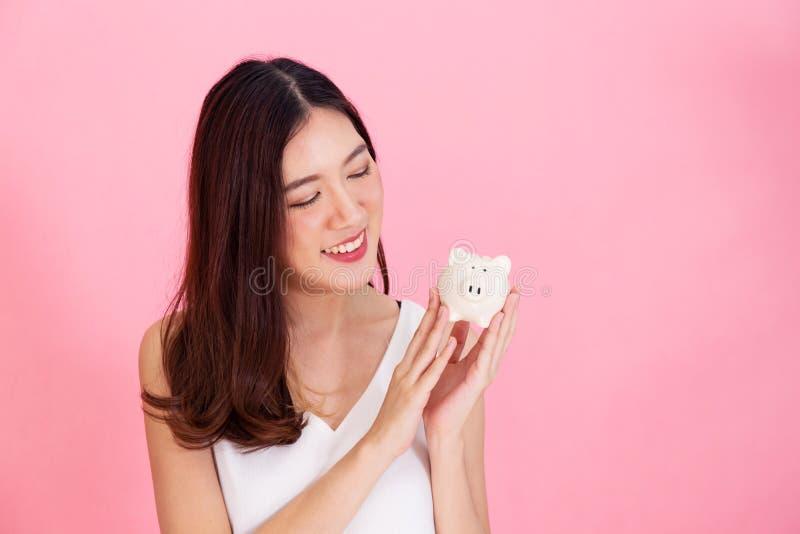 拿着存钱罐的年轻亚裔妇女画象,愉快和激动在自己的在生动的桃红色背景的挽救 免版税图库摄影