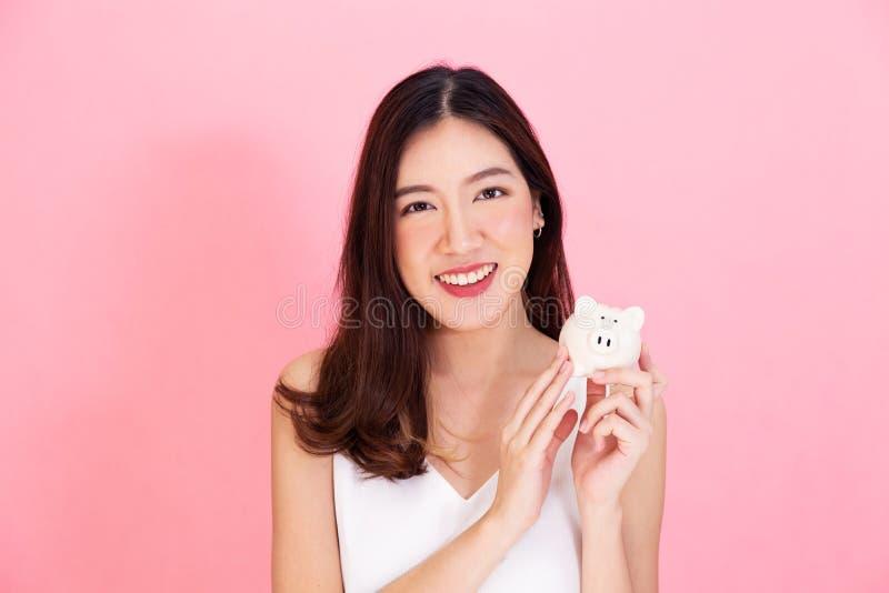拿着存钱罐的年轻亚裔妇女画象,愉快和激动在自己的挽救被隔绝在生动的桃红色背景 免版税库存照片