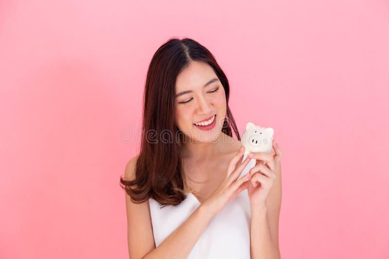 拿着存钱罐的年轻亚裔妇女画象,愉快和激动在自己的挽救被隔绝在生动的桃红色背景 库存图片