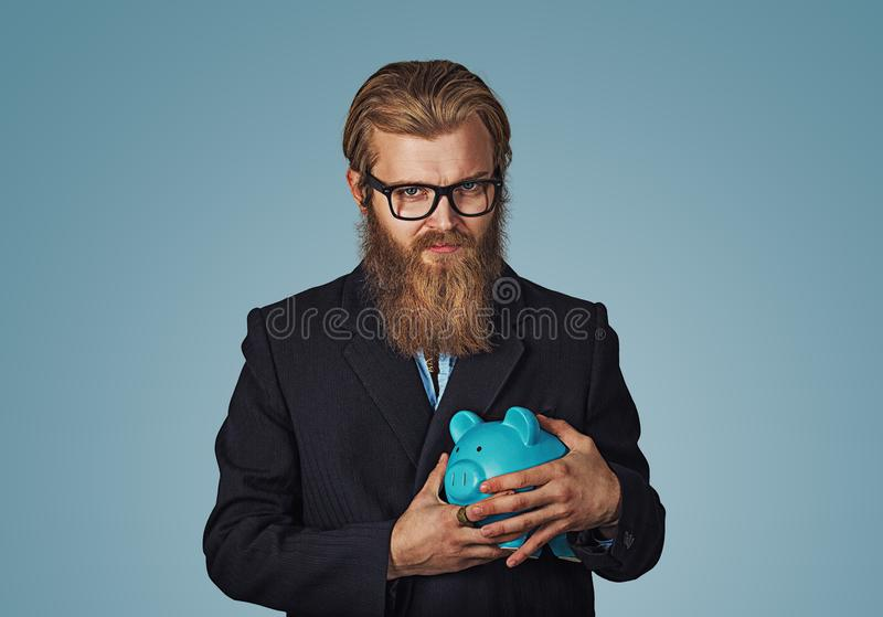 拿着存钱罐的年轻贪婪的心狠商人 图库摄影