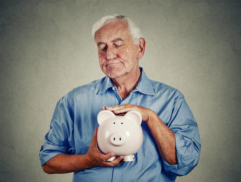拿着存钱罐的老人 库存照片