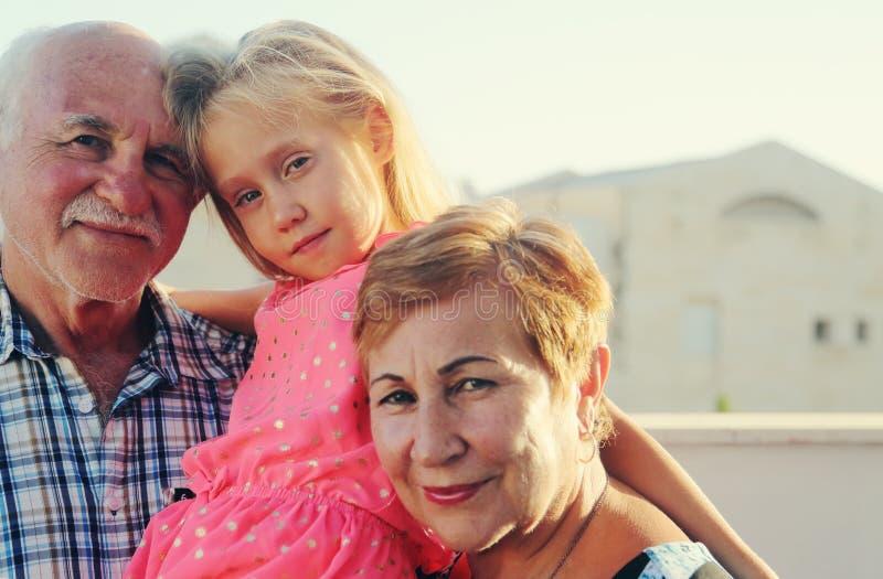 拿着孙女的祖父和祖母 免版税库存照片