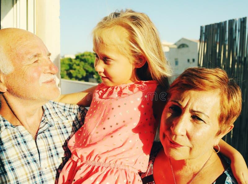 拿着孙女的祖父和祖母 免版税库存图片