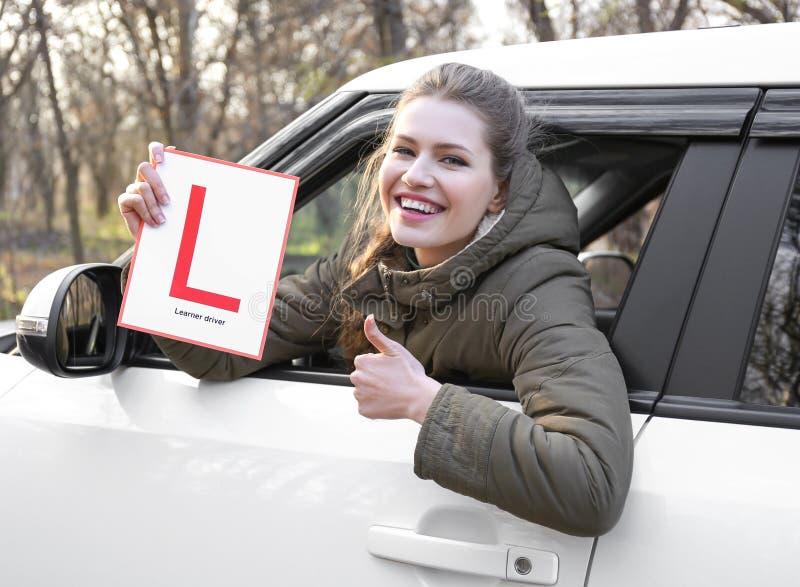 拿着学习者司机标志的少妇,当看时 免版税库存图片