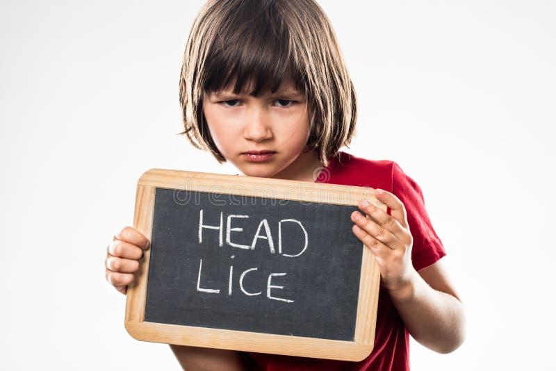 拿着学校板岩的不快乐的幼儿当医疗保健盾 库存照片