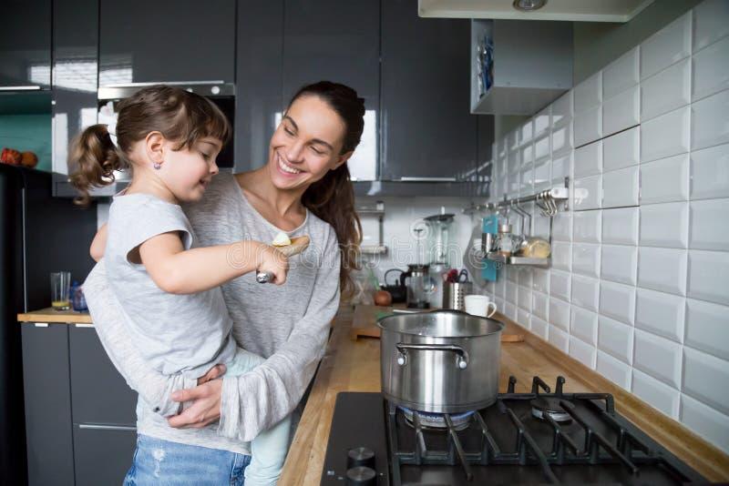 拿着孩子女儿的微笑的妈妈好奇对烹调在kitche 免版税库存图片