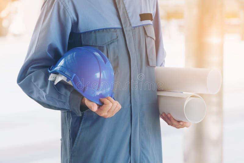 拿着安全帽和图纸的工程师 免版税图库摄影