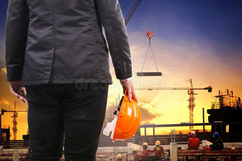 拿着安全帽和工作在修造的工程学人co 免版税库存图片