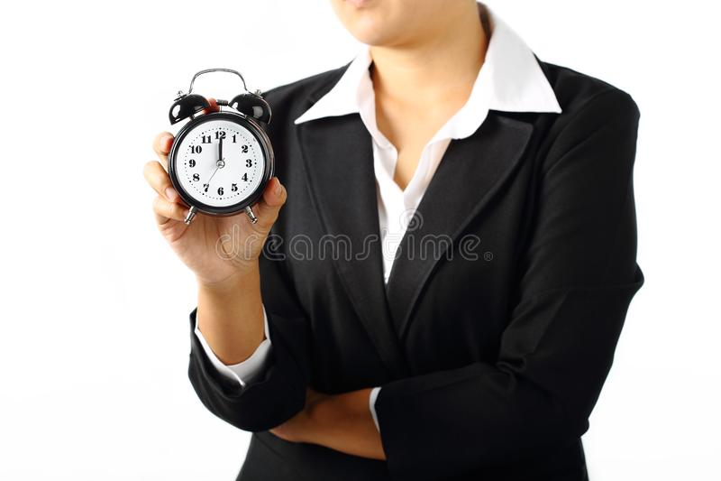 拿着定时器警报上午12点的女实业家 库存图片
