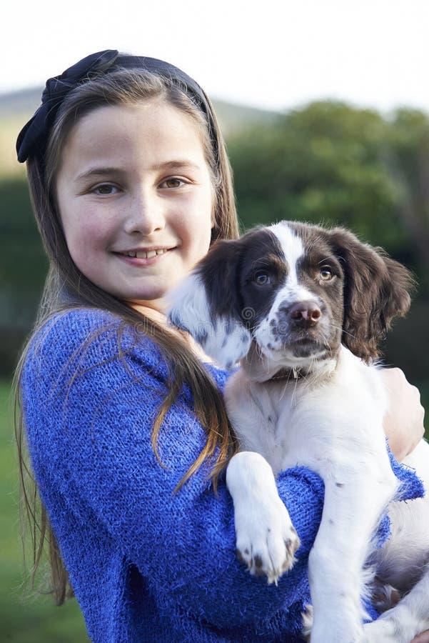 拿着宠物西班牙猎狗小狗的女孩户外在庭院里 免版税库存图片
