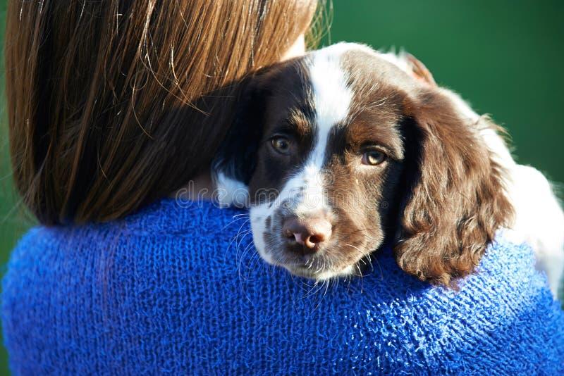 拿着宠物西班牙猎狗小狗的女孩户外在庭院里 图库摄影