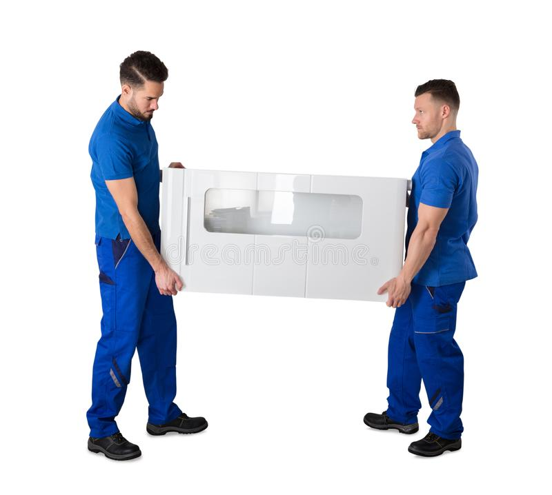 拿着家具的两名搬家工人侧视图  免版税图库摄影