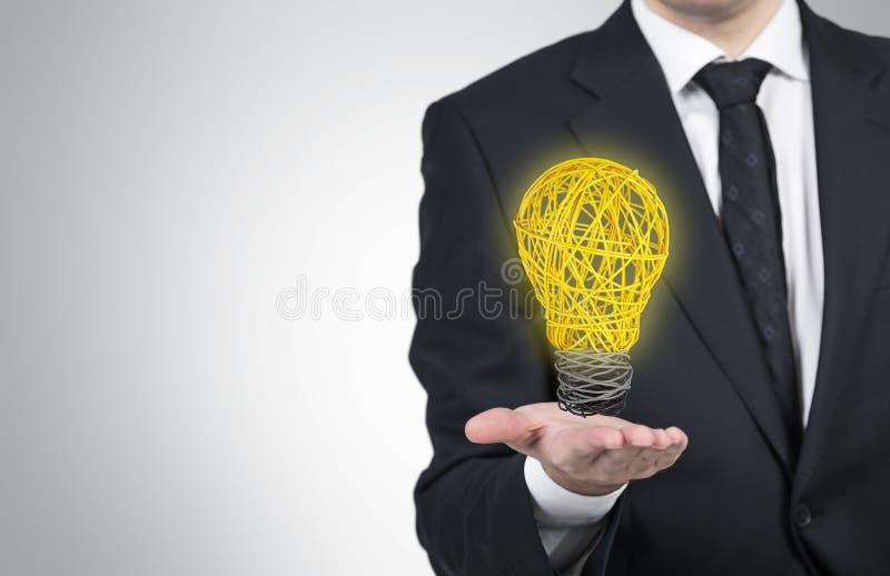 拿着导线的电灯泡人 免版税库存图片