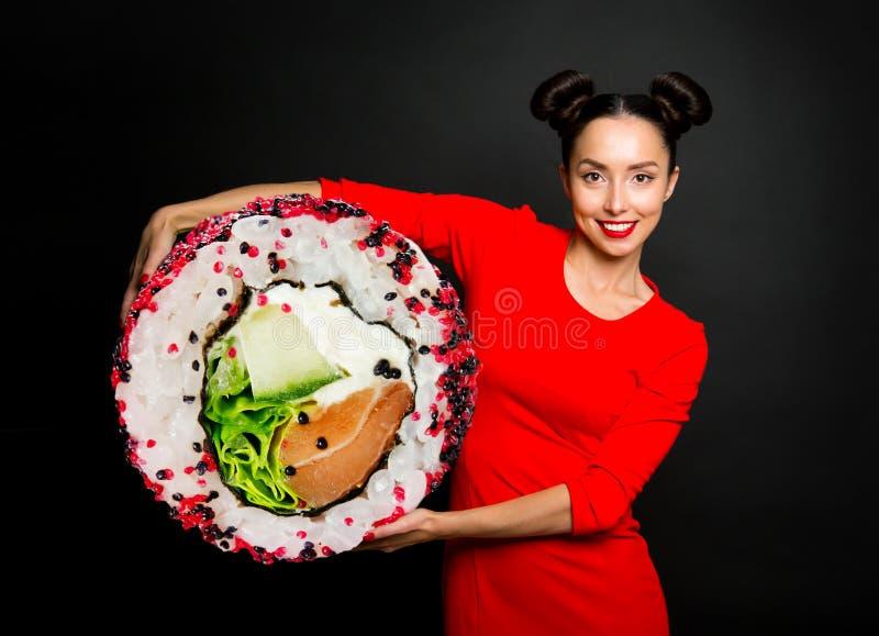 拿着寿司的年轻美丽的妇女 免版税库存照片
