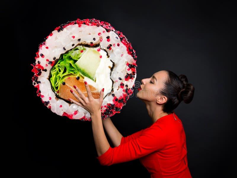 拿着寿司的年轻美丽的妇女 库存照片