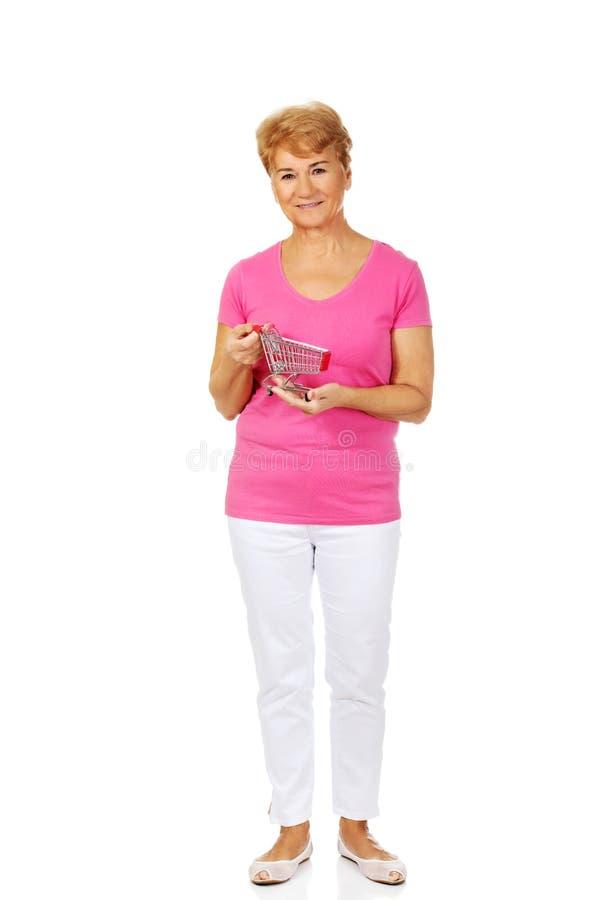 拿着小台车的资深微笑的妇女 库存照片